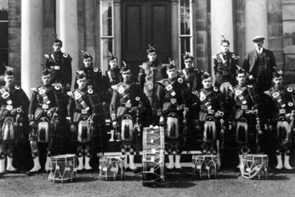 Colinton and Currie Pipe Band. 15 members of band in uniform with instruments plus secretary and Colinton House. Back Row: T. Crabbe; D. Michie; A. Hamilton; J. Corse; W. Allison; J. Todd; J. Ferguson (Secretary). Front Row: A. Thomson; J. Neill; W. Haston; W. Currie; R. Tweedie; Collins; Rae; J Neill, 1925.